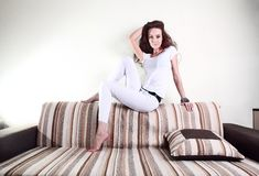 Fashion white woman, sitting on the couch, brown beautiful long hair in white shirt Royalty Free Stock Images