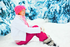 Fashion winter happy smiling woman sitting near branch christmas tree on snow wearing colorful knitted hat in snowy. Day Royalty Free Stock Photo