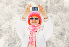 Fashion winter happy woman taking photo self portrait on smartphone over snowy tree. S Royalty Free Stock Photos