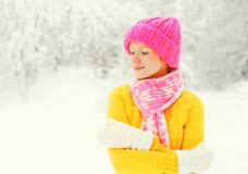 Fashion winter happy woman wearing colorful knitted hat, sweater, scarf enjoys over snowy forest park background Stock Photography