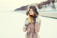 Fashion winter portrait beautiful young woman wearing a coat jacket hat over snow Royalty Free Stock Image