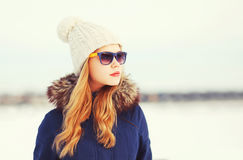 Fashion winter portrait pretty blonde woman wearing a jacket hat and sunglasses looks away over snowy Stock Images