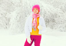 Fashion winter smiling woman wearing colorful knitted hat scarf having fun over snowy Stock Photography