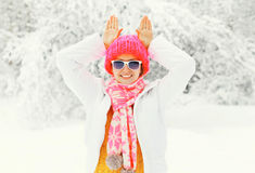 Fashion winter smiling woman wearing colorful knitted hat scarf having fun showing ears rabbit over snowy background Royalty Free Stock Photos