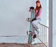 Portrait of a beautiful redhead girl in winter hat and goggles posing with a snowboard while sitting on a railing near royalty free stock photos