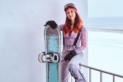 Portrait of a beautiful redhead girl in winter hat and goggles posing with a snowboard while sitting on a railing near royalty free stock images