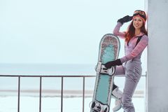 Portrait of a beautiful redhead girl in winter hat and goggles posing with a snowboard while sitting on a railing near royalty free stock image
