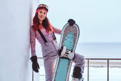 Portrait of a beautiful redhead girl in winter hat and goggles posing with a snowboard while sitting on a railing near stock photos