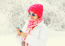 Fashion winter woman using smartphone wearing colorful knitted hat scarf over snowy Royalty Free Stock Images