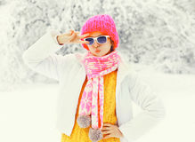 Fashion winter woman wearing a colorful knitted hat scarf having fun over snowy tree Royalty Free Stock Photo