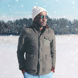Fashion winter young african man wearing a sunglasses jacket with knitted hat over snowflakes Stock Photo