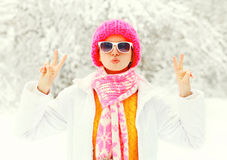 Fashion winter young woman wearing colorful knitted hat, scarf having fun over snowy forest park background. Fashion winter young woman wearing colorful knitted Stock Photos