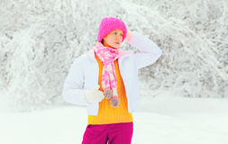 Fashion winter young woman wearing colorful knitted hat scarf over snowy Royalty Free Stock Photos