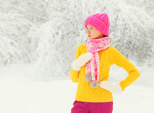 Fashion winter young woman wearing colorful knitted hat, sweater, scarf over snowy forest park background Stock Photos