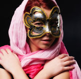 Fashion woman. With pink scarf and carnival mask on black background Stock Photos
