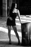 Fashion woman. Brunette in evening dress posing in an old factory and relies on a garbage can Stock Photo