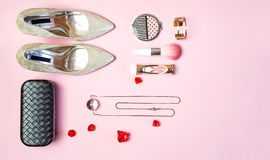 Flat lay women party outfit gold colored shoes accessories jewelry clutch makeup cosmetic brushes pastel pink. Flat lay top view stock photo
