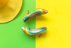 Fashion woman accessories set. Trendy fashion colorful shoes heels, stylish yellow big hat. Colorful green and yellow background. Lifestyle Concept royalty free stock photos