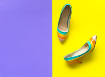 Fashion woman accessories set. Trendy fashion colorfull shoes heels oh the purple and yellow background royalty free stock photography