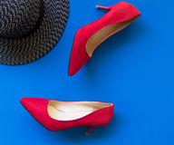 Fashion woman accessories set. Trendy fashion red shoes heels, stylish big hat. blue background.
