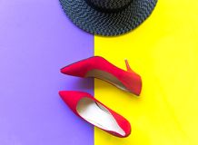 Fashion woman accessories set. Trendy fashion red shoes heels, stylish big hat. Colorful purple and yellow background. stock image