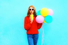 Fashion woman with an air balloons holds cup of fruit juice. On blue background Royalty Free Stock Images