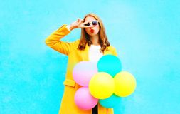 Fashion woman with an air balloons in a yellow coat Royalty Free Stock Image