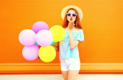 Fashion woman with an air colorful balloons sends an air kiss. On orange background Stock Photos