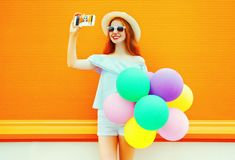Fashion woman with an air colorful balloons takes a picture self portrait on a smartphone Stock Photography