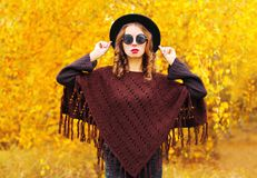 Fashion woman in autumn day wearing a black round hat, knitted poncho. On a yellow leaves background stock photos