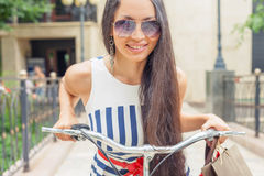 Fashion woman with bags and bike, shopping travel to Italy. Closeup fashion woman dressed in striped dress with bags and vintage bike has shopping travel to Royalty Free Stock Image