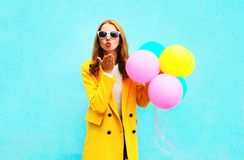 Fashion woman with balloons sends an air kiss in a yellow coat. On colorful blue background Royalty Free Stock Photo