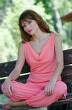 Fashion woman on the bench , with a pink piece garment. Fashion woman sitting squatting on the bench wear a pink piece garment. Nice romantic outdoor photo of a stock photo