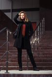 Fashion woman in black coat walking on night city street Stock Photos