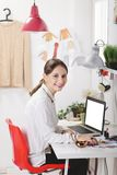 Fashion woman blogger working in a creative workspace. Young creative woman typing on a laptop in her office royalty free stock photo
