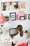 Fashion woman blogger working in a creative workspace. Young creative woman typing on a laptop in her office stock image