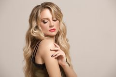 Fashion woman blond with long wavy hair. Woman with beautiful makeup royalty free stock images