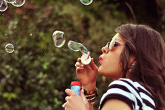 Fashion woman blowing bubbles. Fashion girl blowing bubbles in the wind Stock Images