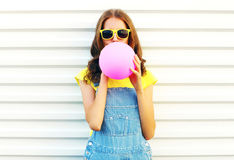 Fashion woman blowing a pink air balloon on white background Stock Photo