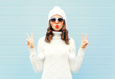 Fashion woman blowing red lips makes air kiss wearing a heart shape sunglasses, knitted hat, sweater over blue Stock Images