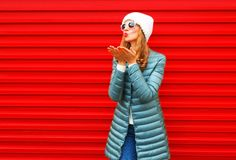 Fashion woman is blowing red lips sends an air kiss. On a background Stock Photography