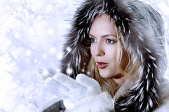 Fashion Woman Blowing Snow. Fashion Woman with perfect skin Blowing Snow on blue background. She in white fur coat and Stock Photo