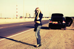 Fashion woman with broken car calling on the phone Royalty Free Stock Photo