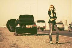 Fashion woman calling on cell phone next to broken car. Fashion blond business woman calling on cell phone next to broken car Stylish female model in dark blue stock images
