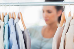 Fashion woman choosing clothes on clothes rail Royalty Free Stock Photos