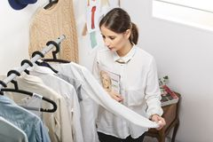 Fashion woman choosing a piece for the new collection. Fashion woman with magazine working in her office royalty free stock photography