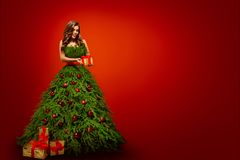 Fashion Woman in Christmas Tree Dress, Model hold Xmas Present royalty free stock image
