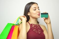 Fashion woman with closed eyes kissing credit card and holdings colorful shopper bags on white background. Copy space. Fashion woman with closed eyes kissing Stock Image