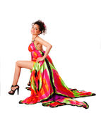 Fashion woman in colorful dress. Beautiful happy smiling Caucasian Hispanic Latina fashion model woman wearing colorful dress, sitting showing leg, isolated royalty free stock image