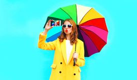 Fashion woman with colorful umbrella taking selfie by smartphone. On blue wall background royalty free stock photos